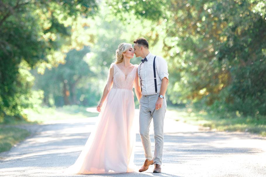 Bräutigam im Anzug küsst die Braut mit Haarkranz nach der freien Trauung.