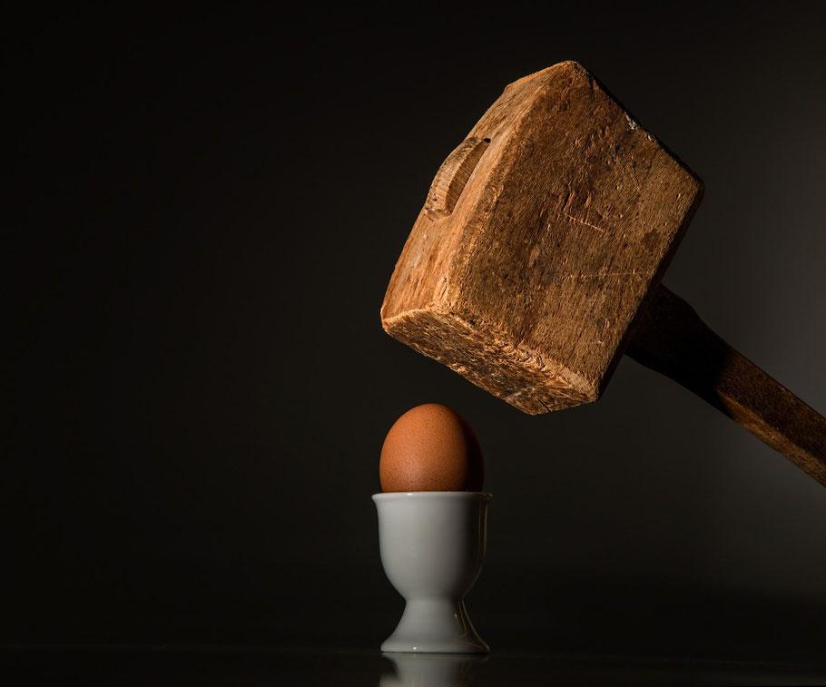 Hammer über einem Ei