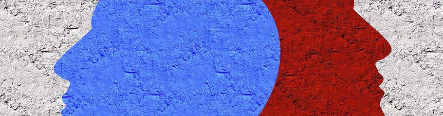 Zwei plakativ auf eine Wand gemalte Köpfe in Blau und Rot. Streit, Funkstille, Wegsehen.