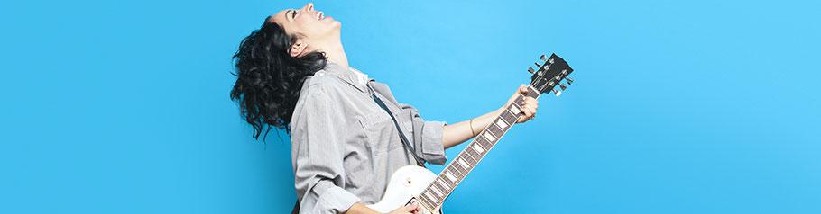 Dunkelhaarige Frau spielt enthusiastisch Gitarre. Freies Selbstsein durch Coaching.