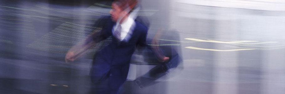 Ein Mann im Anzug springt mit seinem Aktenkoffer über die Srasse