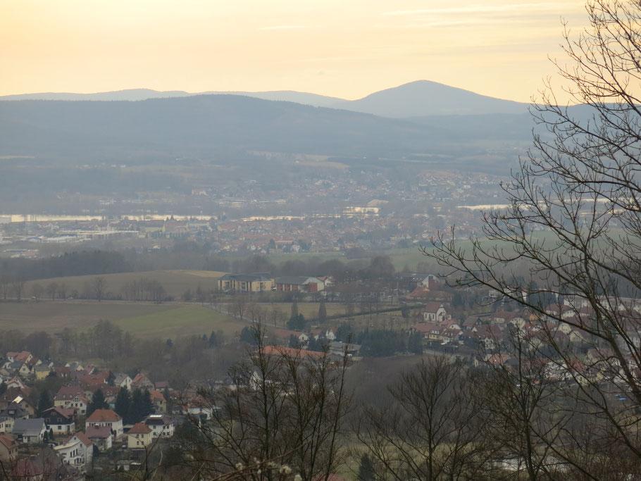 Häuser, Wiesen und Gewässer, im Hintergrund Berge, im Sonnenuntergang