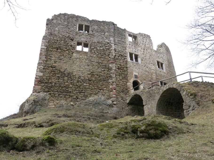 Gemäuer der Burgruine in Bad Liebenstein von vorne. Zu sehen sind grobes Mauerwerk, teilweise brüchig, leere Fenster, der Zugang über zwei Brückenbögen.