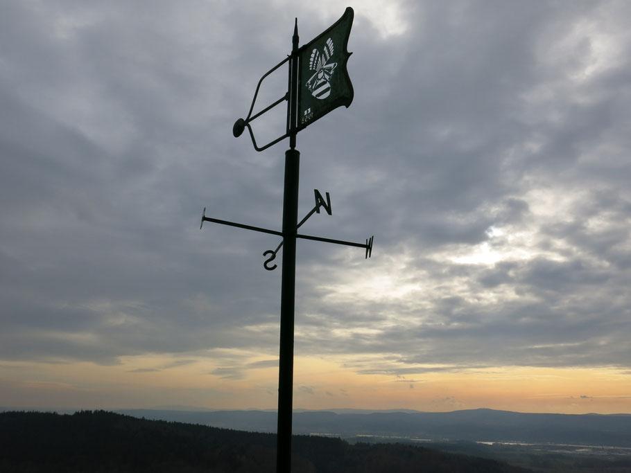Wetterfahne mit Himmelsrichtungen, im Hintergrund Berge, Gewässer im Sonnenuntergang.