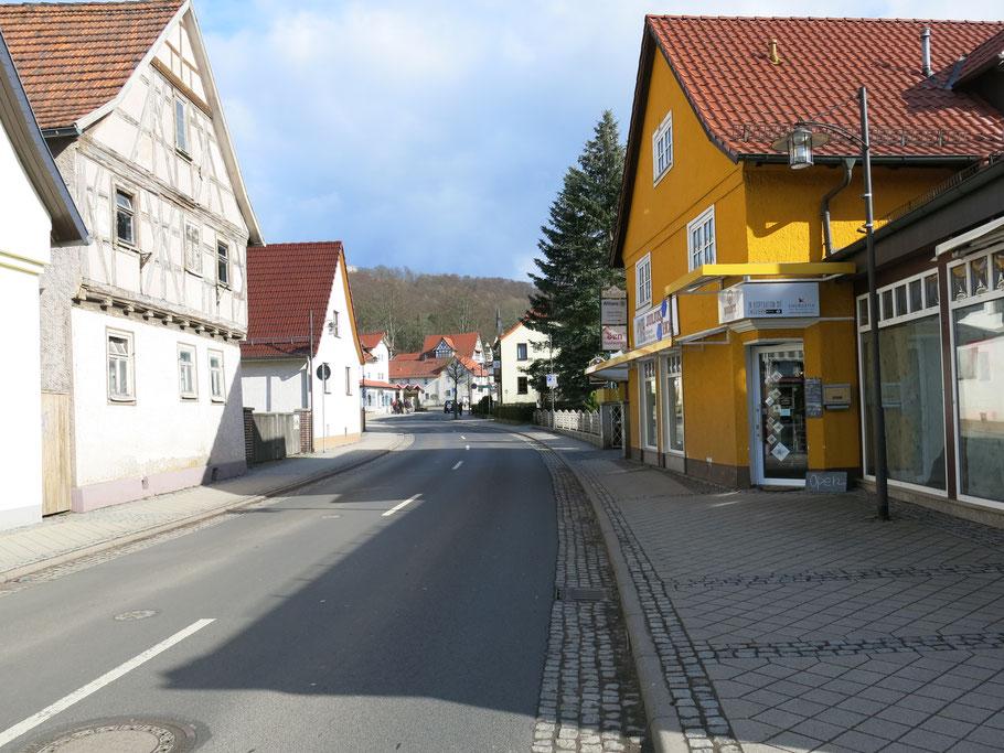 Blick auf eine nahezu leere Straße in Bad Liebenstein mit Wohnhäusern und Geschäften.