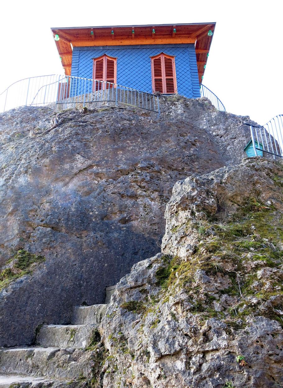 Chinesisches Teehaus mit blauen Schindeln und rotbraunen Fenstern. Das Gebäude ist auf einem Fels, der durch eine geschwungene, grobe Steintreppe erreichbar ist.