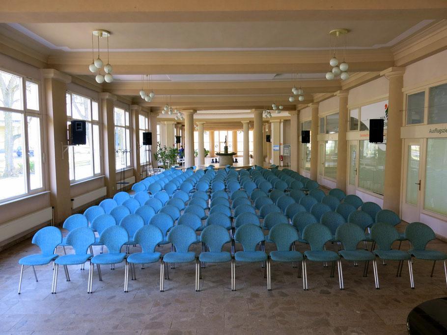 Blick in die Wandelhalle in Bad Liebenstein, zu sehen sind Stuhlreihen, die Fensterfront, der Brunnen am Ende der Halle und die Säulen sowie seitliche Ausstellungsräume.