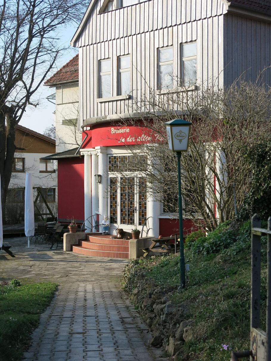 Blick auf den Eingang der alten Kapelle, Brasserie/Restaurant in Bad Liebenstein. Ein Hund liegt auf den Treppenstufen.