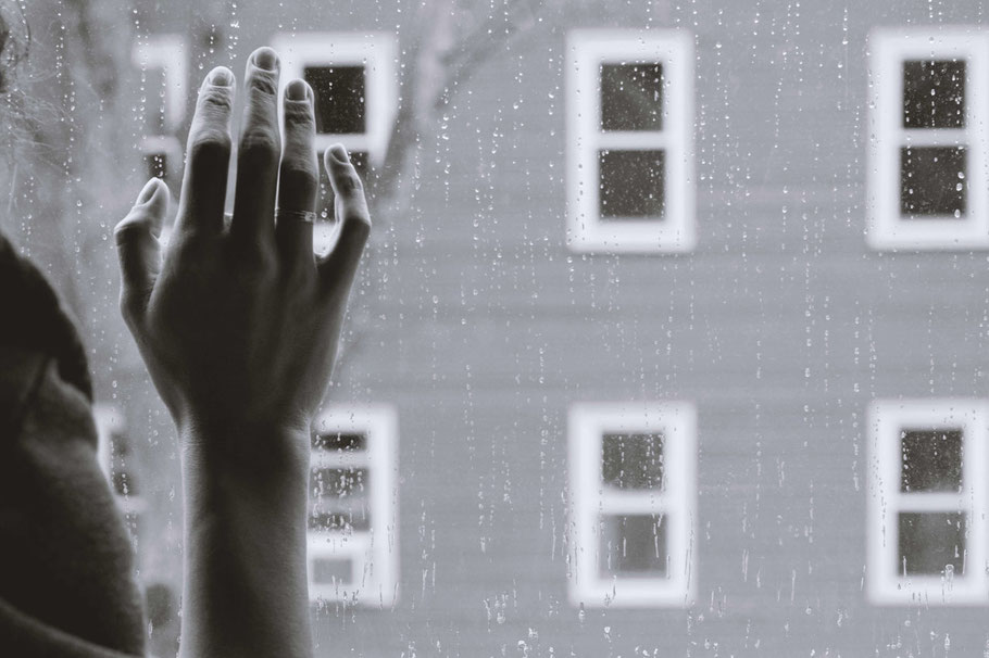 Hand on Window with Raindrops