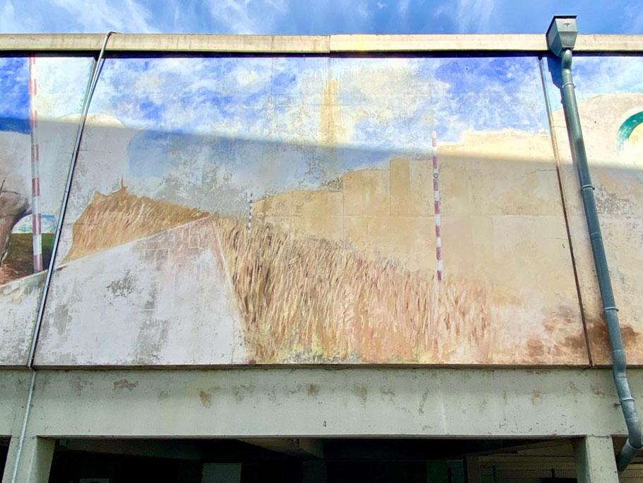 """Mittlerer Motivausschnitt des dreiteiligen Wandbilds """"Oberneulander Vergangenheit und Gegenwart"""": Eine Trasse zerschneidet ein Kornfeld, am Rand ist die Silhouette der Stadt zu erkennen (Foto: 06-2020, Jens Schmidt)"""