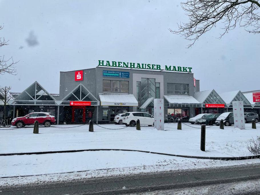 Winter 2021: Habenhauser Markt mit parkenden Fahrzeugen an der Ernst-Buchholz-Straße in Bremen-Habenhausen, im Hintergrund Sunpoint Sonnenstudio und die Sparkasse Bremen (Foto: 01-2021, Jens Schmidt)