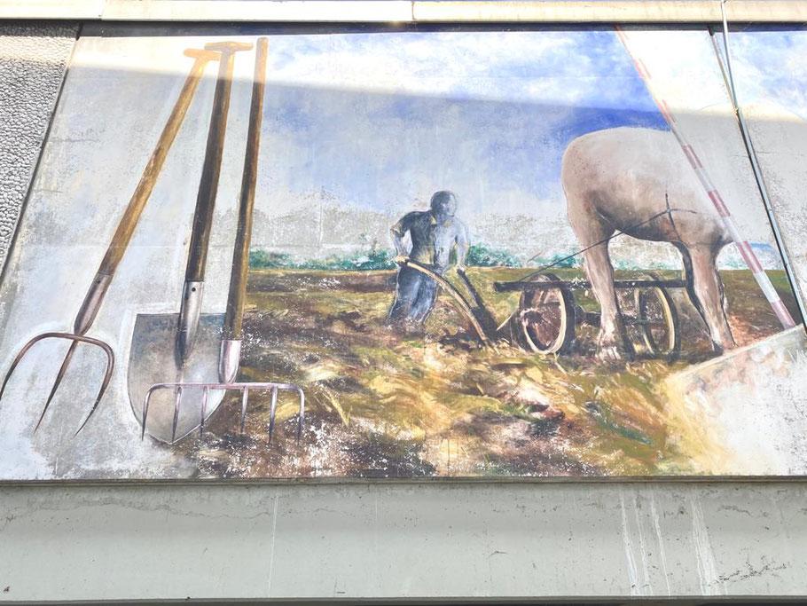 """Linker Motivausschnitt des dreiteiligen Wandbilds """"Oberneulander Vergangenheit und Gegenwart"""": Ein Landwirt pflügt seinen Acker (Foto: 06-2020, Jens Schmidt)"""