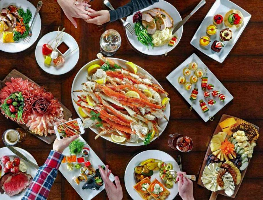 Motoglobe Motorradreisen. Auf dem Tisch stehen diverse Speisen mit Fisch, Fleisch, Gemüse, Sushi, Früchte, Saucen, Brot und Getränke.