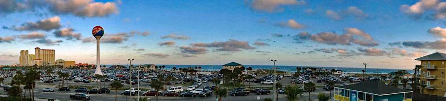 Motoglobe_Motorradreisen. Der grosse Parkplatz ist gefühlt mit vielen Autos und im Hintergrund ist das Meer zu sehen.