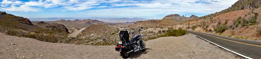 Motoglobe Motorradreisen. Die Harley steht auf einem Kiesplatz auf dem Sitgreaves Pass in Arizona, USA, und im Hintergrund ist die kurvige Strasse und die Wüstenberge zu sehen.