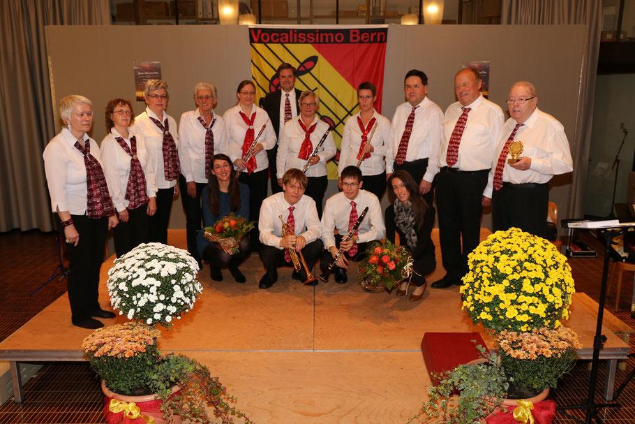 Alle aktiven Musikanten, Sängerinnen und Sänger auf der Bühne; die Damen des instrumentalensembles umgeben von den Sängerinnen und Sängern des Vocalensembels; davor die Solisten und die Pianistin sowie die Herren des Instrumentalensembles.