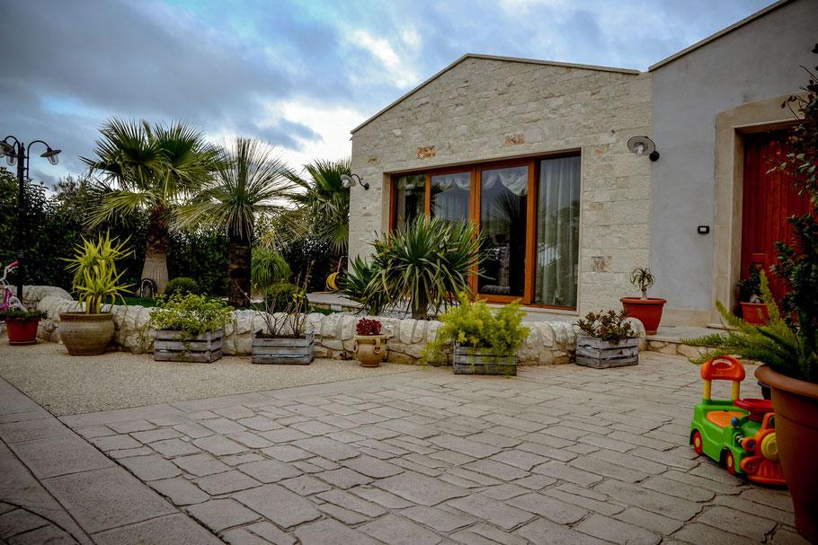 Pavimento stampato effetto pietra naturale di modica o comiso e ghiaia a visto (sasso lavato) con cornici in basole o travertino - Casa rurale in pietra