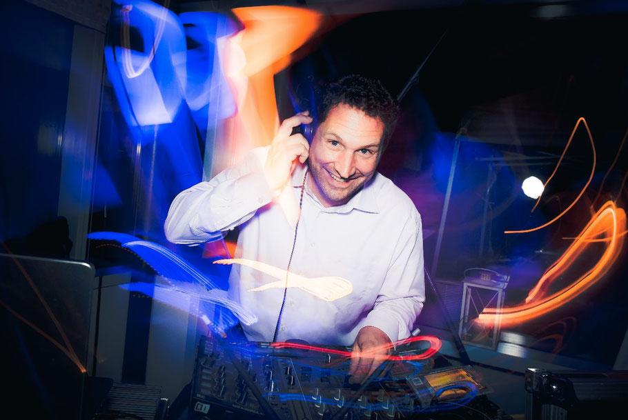 Der DJ mit bunten Lichtern und dem Mischpult