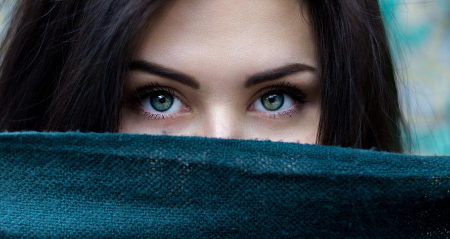 Augen einer Frau, das restliche Gesicht mit einem Tuch verhüllt