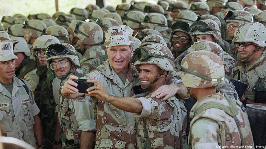 Если это настоящий Буш-старший, то держат они, если присмотритесь, не телефон, а фотоаппарат, поскольку в то время по телефону звонили, а фотоаппараты фотографировали. Идиотизм ситуации в том, что народу море, а они снимают себя сами. А вы сами понимайте.