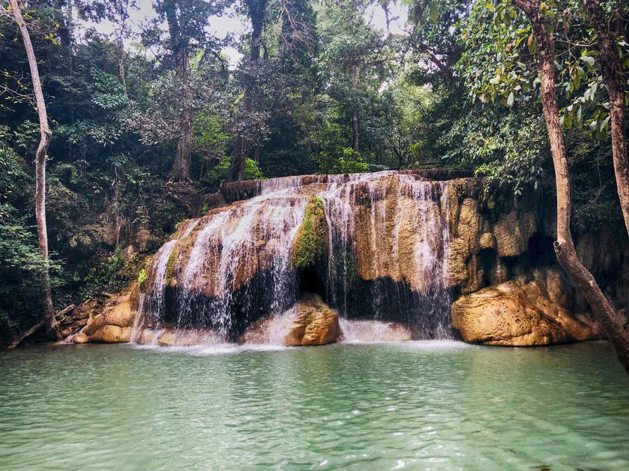 Die Felsen, Pools und Fische des Erawan Wasserfalls verwandeln die Landschaft zu einem spaßigen Wasserpark.