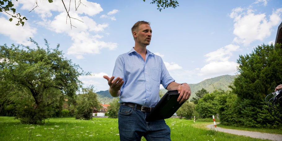 Stefan Klaffenbacher auf einem Baugrundstück mit einer Arbeitsmappe in der linken Hand und einer Sprachgeste mit der rechten Hand