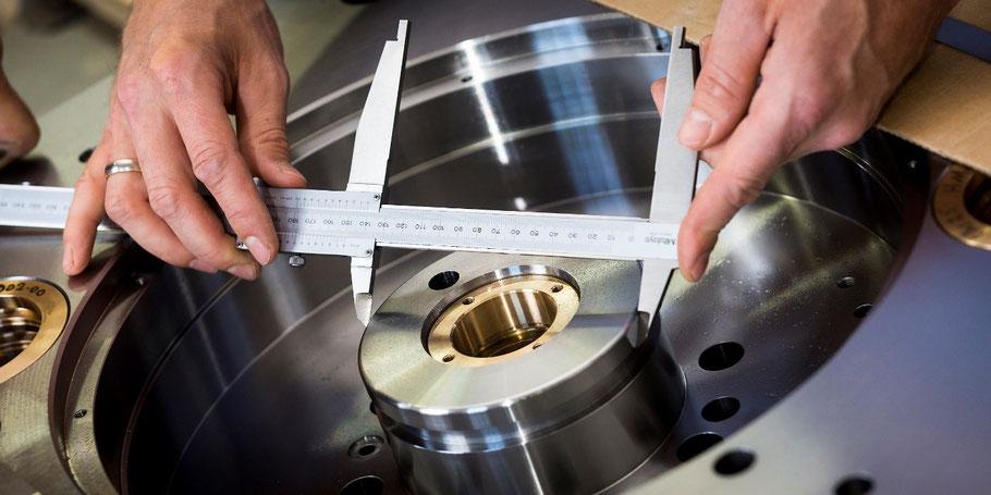 zwei Hände messen mit einer Schubleere an einem Metallwerkstück