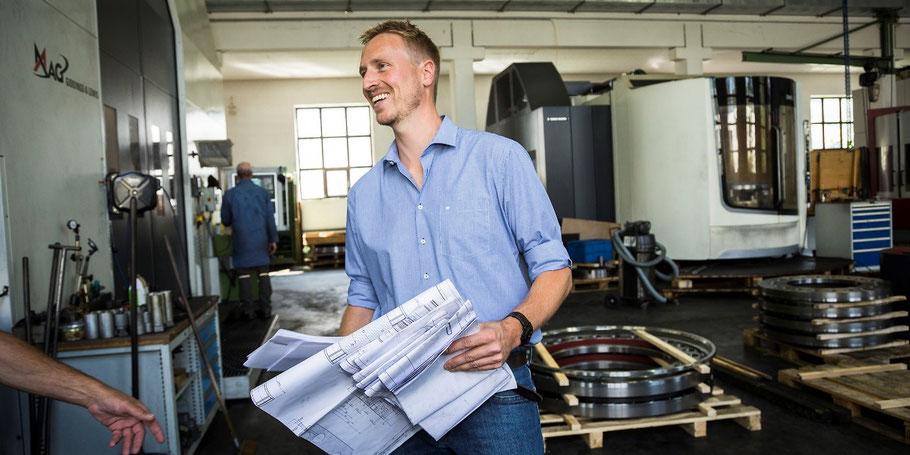 Stefan Klaffenbacher mit einem Arbeitsplan in der Hand in der Werkstatt stehend