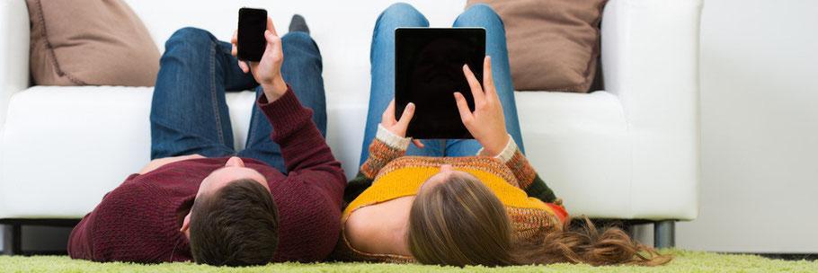 Highspeed Internet bis zum Sofa - zwei Personen surfen mit Smartphone und Tablet im Netz vom Sofa aus