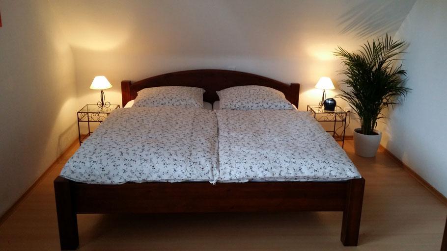 Schlafzimmer mit Doppelbett, Sessel und Kleiderschrank