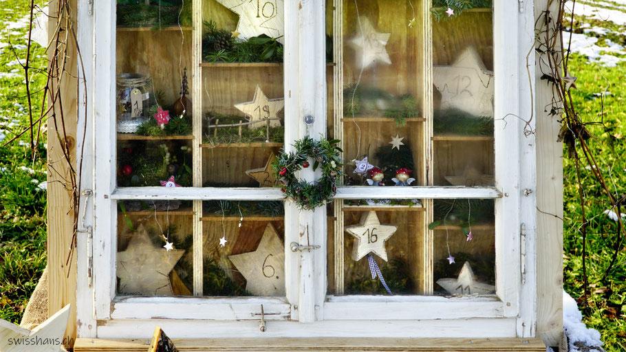 Weihnachtlich geschmücktes Fenster mit Adventskalender-Sternen