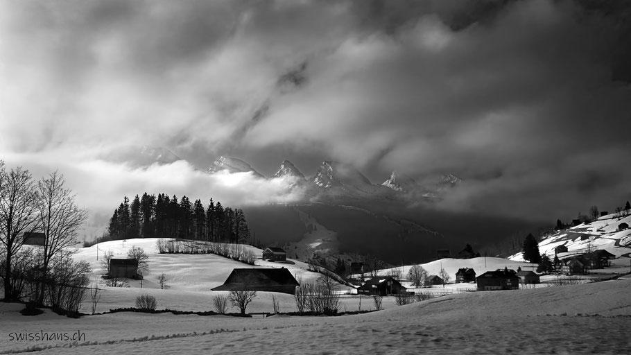 Winterlandschaft im Toggenburg mit Häusern und den Churfirsten im Hintergrund