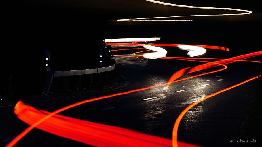 Weisse und rote Streifen von Autos auf der Stossstrasse bei Nacht mit Leitplanken und Strassenpfählen