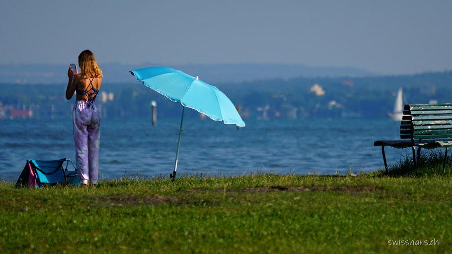 Junge Frau mit Smartphone und Sonnenschirm am Bodensee