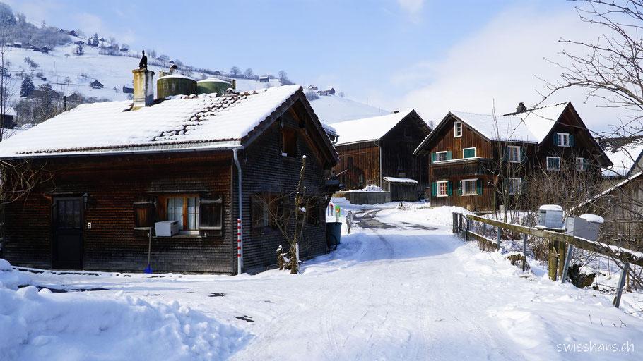 Holzhäuser mit verschneiten Strassen