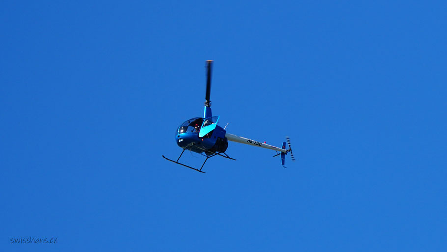 Blauer Helikopter am blauen Himmel. Der Flugbegleiter öffnet die Türe um ein Foto vom 1000-Tonnen Schwerlastkran zu schiessen.
