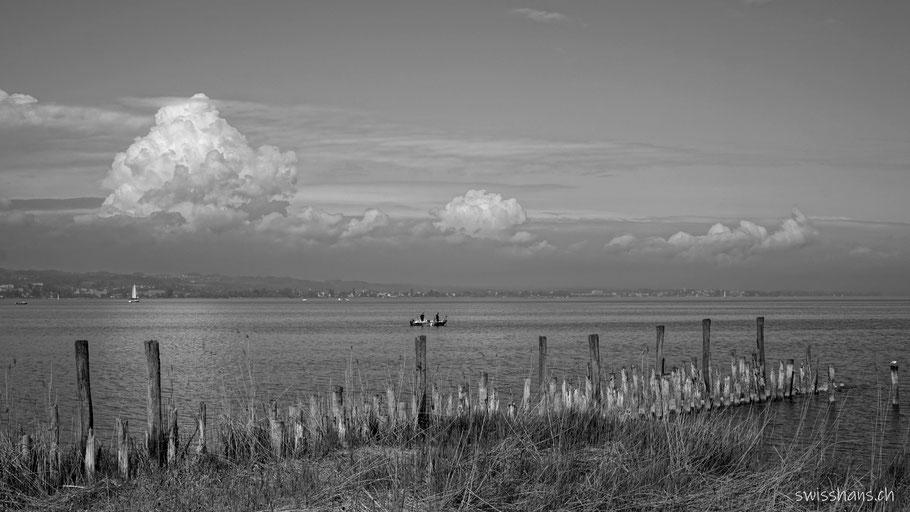 Wellenbrecher am Bodensee mit Fischerboot und attraktiven Wolken