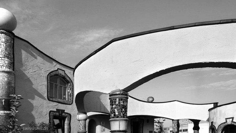 Fassade der Hundertwasser Markthalle Altenrhein mit geschwungenen Elementen und schiefen Fenstern