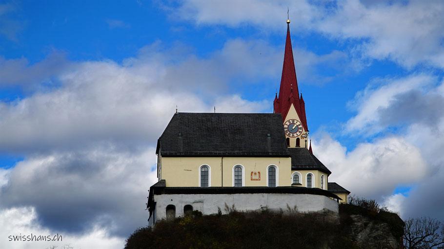 Basilika auf einem Felsen vor Himmel und Wolken in Rankweil