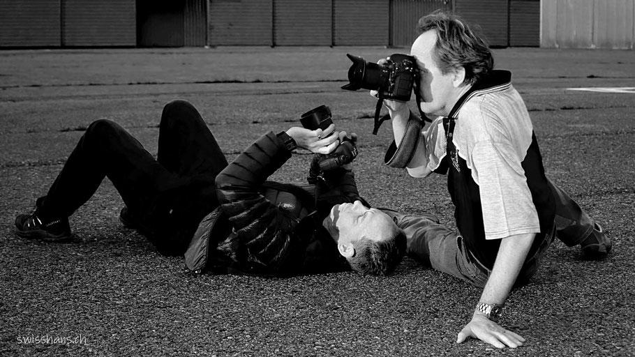 Zwei Fotografen sitzen mit ihren Kameras auf der Piste des Flugplatzes Hohenems