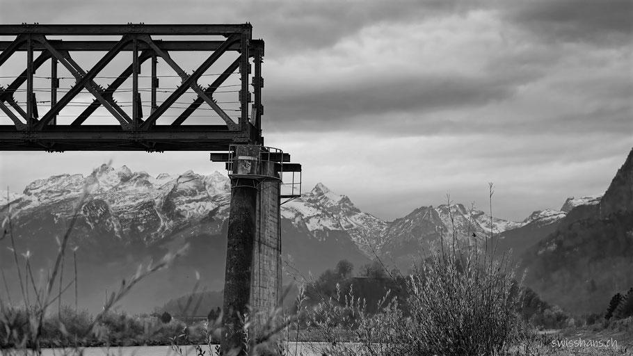 Alte Stahlkonstruktion der Dienstbahnbrücke vor den winterlichen Bergen und den grauen Wolken