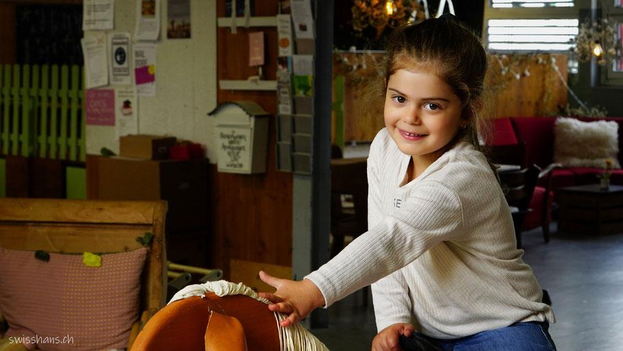 Mädchen sitzt auf dem Holzpferd in der Spielecke der Kreativhalle Setzchaschte in Grabs.