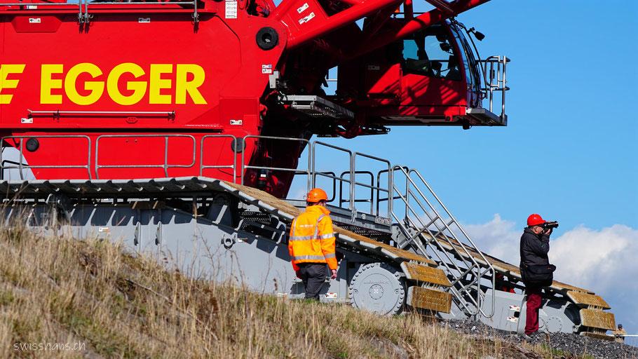 Ein Arbeiter und ein Fotograf stehen vor einem 1000-Tonnen Schwerlastkran von Emil Egger AG. Die Kranraupen sind riesig.