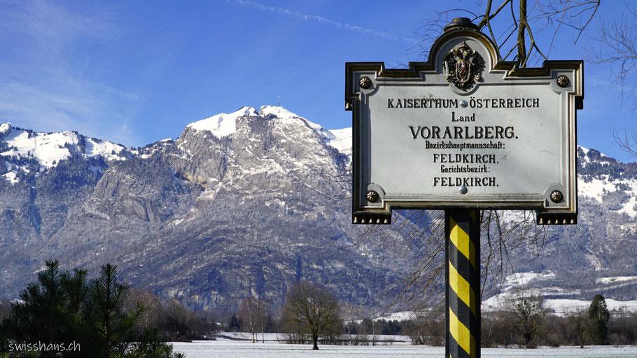 Antike Grenztafel im Ruggeller Riet mit Schweizer Bergen im Hintergrund
