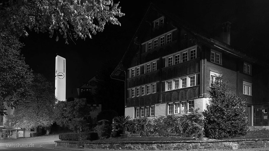Altes Haus und Kirchturm der katholischen Kirche von Rebstein als Nachtaufnahme