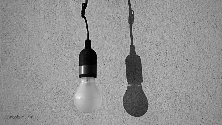Glühlampe mit Fassung wirft eigenen Schatten an die Wand