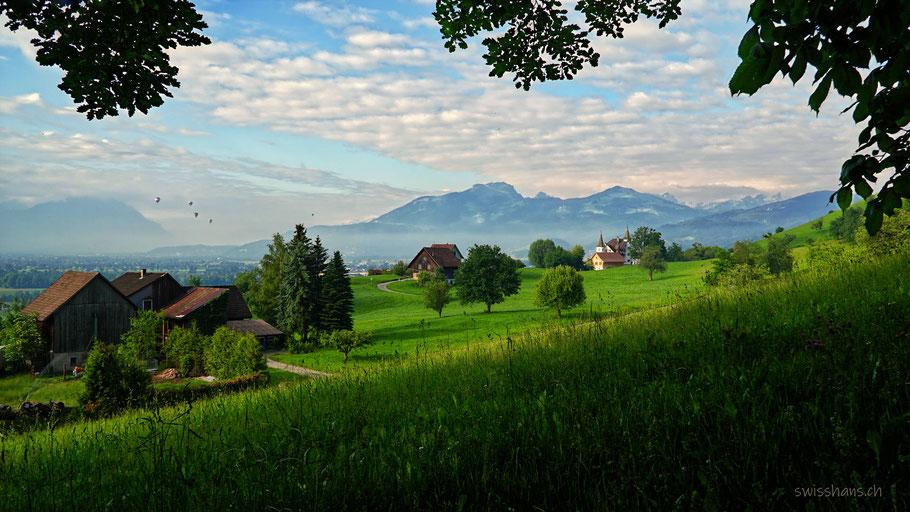 Blick auf das Rheintal mit Wiesen, Bauernhäusern und Schloss Weinstein. Blauer Himmel mit Schäfchenwolken und Luftballonen