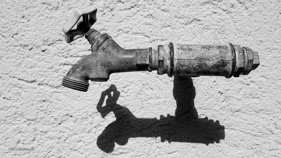 Wasserhahn mit Schatten an der Wand