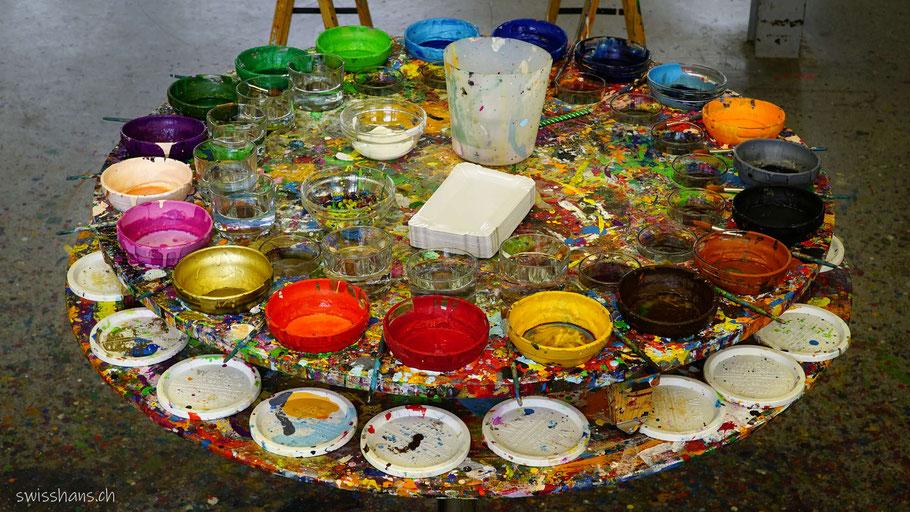 Tisch mit bunten Farbtöpfen in der Kreativhalle Setzchaschte in Grabs.