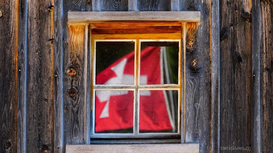 Holzfassade mit Fenster. Schweizerfahne spiegelt sich im Fenster